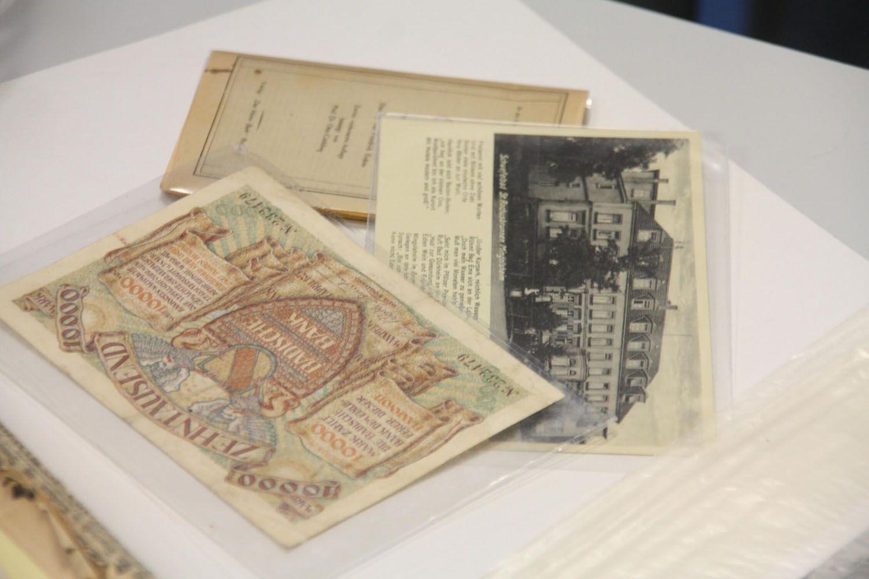Historische Dokumente wie alte Banknoten, Fotos und Zeitungsberichte, geschützt in Plastikhüllen.