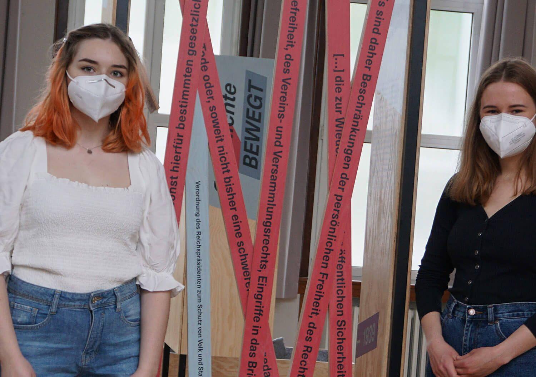 Zwei junge Peer-Guides stehen neben einer der Stationen unseres mobilen Geschichtlabors