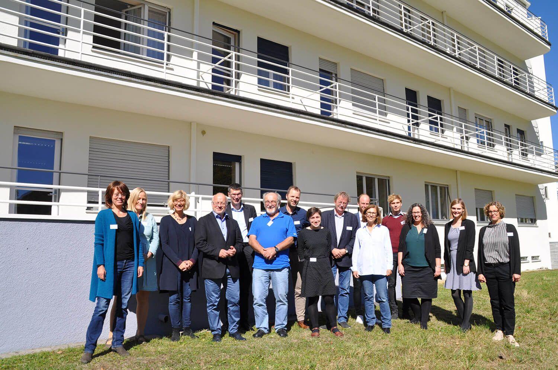 """Gruppenfoto von Teilnehmer:innen der Fachtagung """"Gedenkstätten an Orten früher Konzentrationslager"""" draußen vor einem Gebäude"""